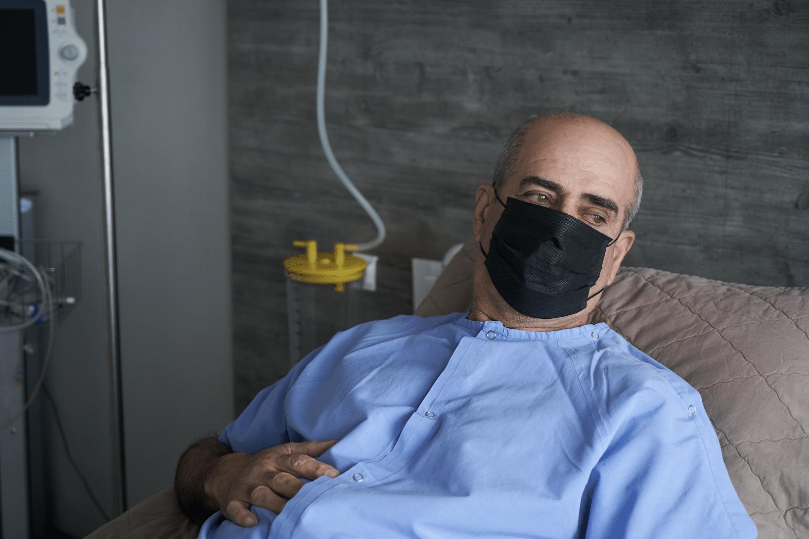 older-man-with-face-mask-on-hospital-bed