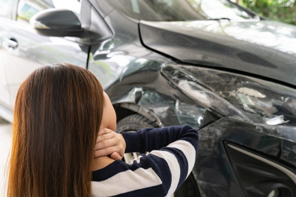 Woman with dark hair standing in front  of crashed car grasping neck while she appears to be in pain.