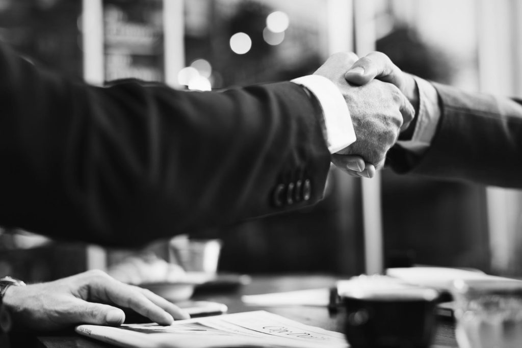 black and white photo of two attorneys shaking hands after finishing negotiations