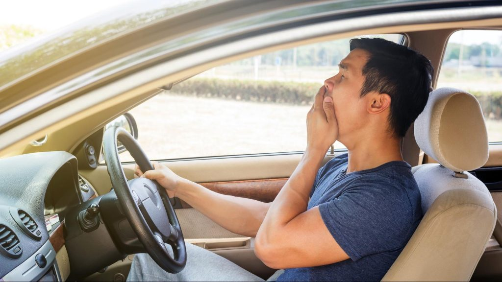 A drowsy driver yawns as he is about to fall asleep behind the wheel