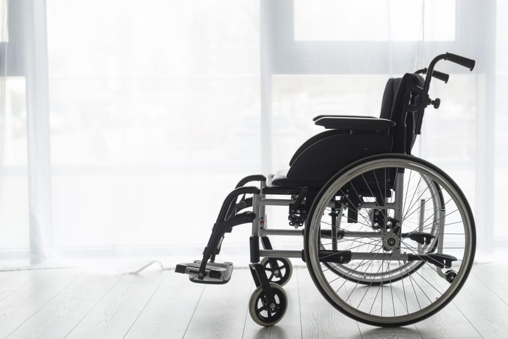 an empty wheelchair on a wood floor in front of a brightly lit window with sheer white curtains