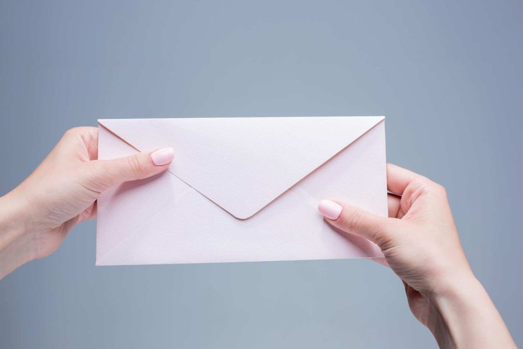 close up of hands holding an envelope to send through the mail
