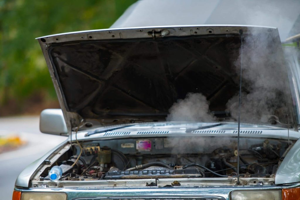 a car with an overheating engine and an open hood allowing smoke to escape