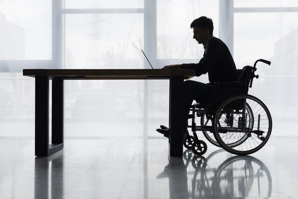silhouette of a man in a wheelchair at a table using a laptop computer