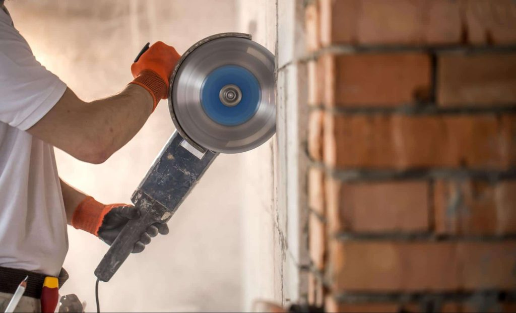 A construction worker uses an angle grinder to cut the mortar in a brick wall. Some jobs require working with dangerous tools. If a workplace injury happens, the workers are covered by workers compensation.