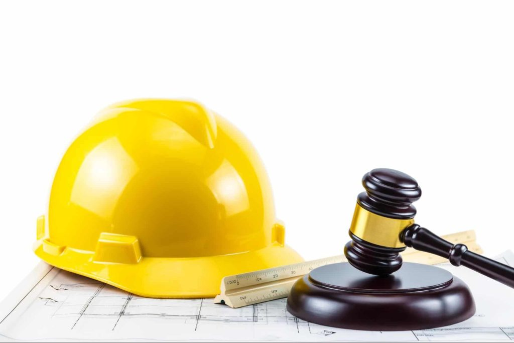 A construction worker's hard hat and a judge's gavel on a white background. Injured workers can receive help on their worker compensation claim from an attorney.