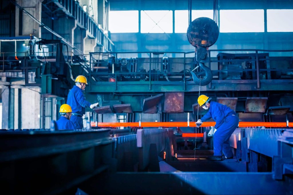 Three steel mill workers operating heavy machinery. Employees who are injured at work in dangerous jobs like this would receive a workers' compensation settlement.