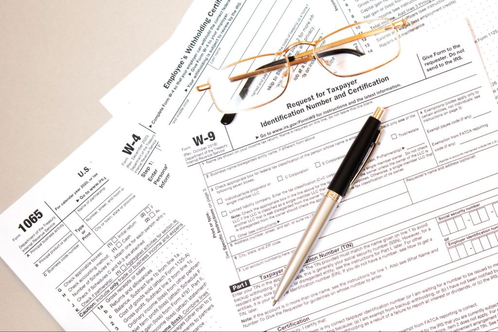 Federal tax forms on a table with glasses and a pen. Filing taxes can be confusing and if you have a workers compensation payments it may make you more confused about how to file.