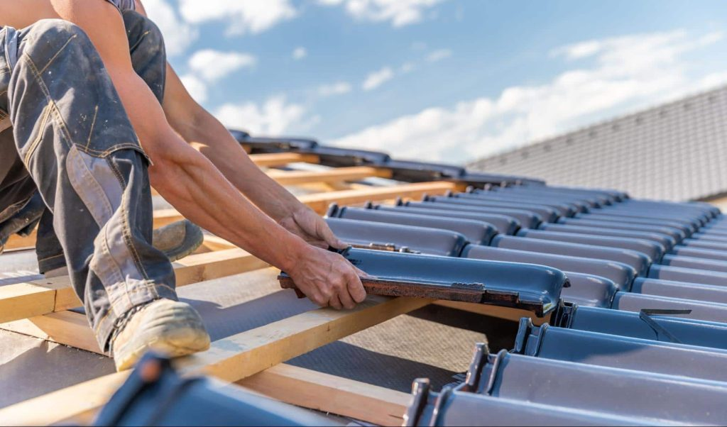 A roofer places tiles on a new roof. If the roofer gets injured at work, they may require a workers' compensation settlement.
