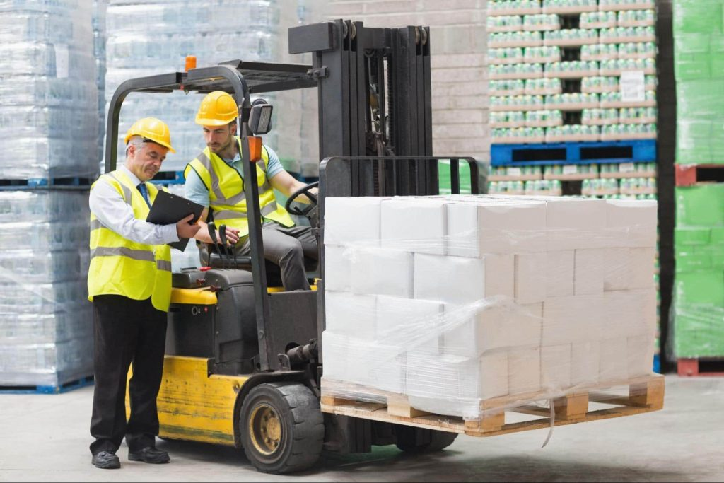 A forklift operator stops to speak with his supervisor. If the forklift operator is injured at work he would need to report the injury to human resources or a safety officer to file a workers comp claim.