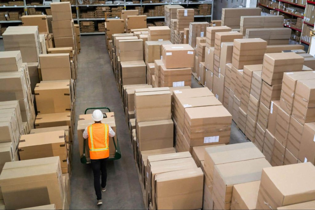 A worker pushes a cart with boxes through a warehouse.