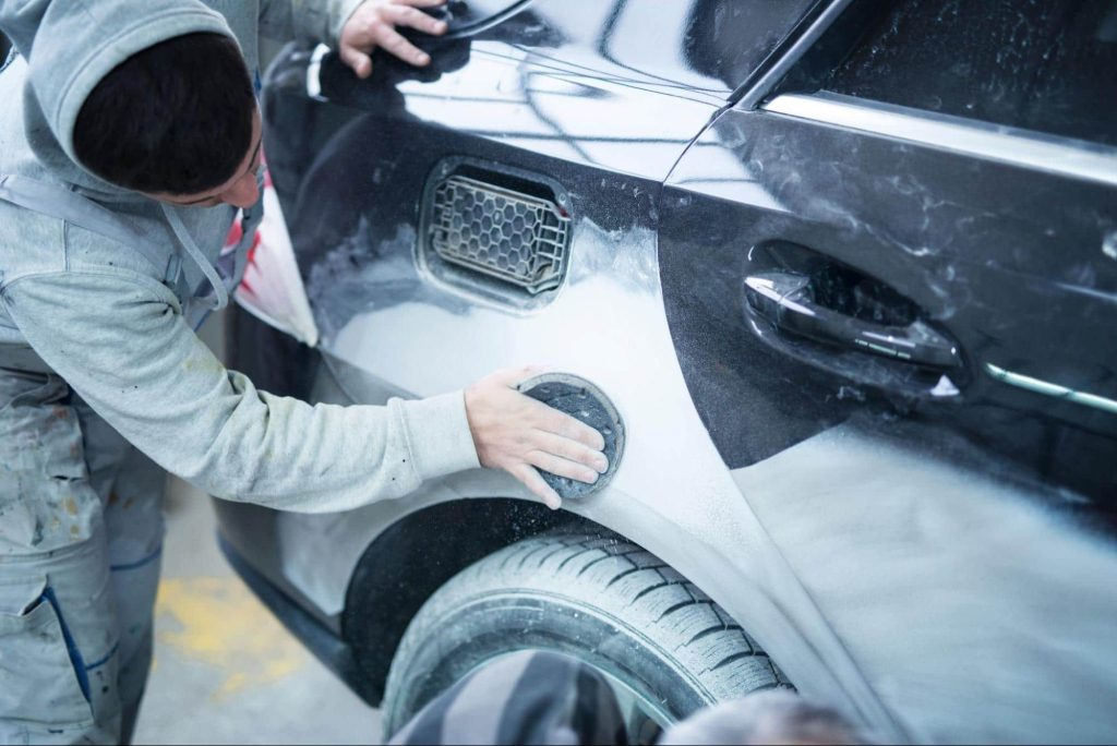 A body shop technician repairs the rear door and fender of an SUV after an accident. While the car has been restored, there will still be some loss of value since the accident goes on the vehicle history report for the car.