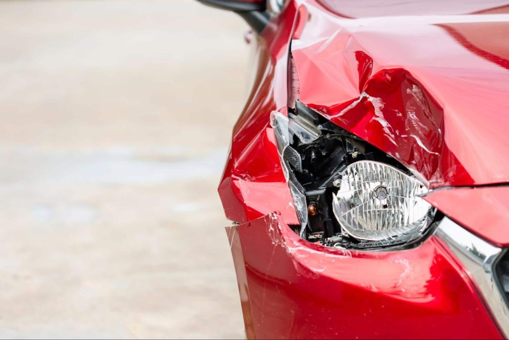 Close up of a car with a damaged headlight and front fender. Damage from a car accident will diminish the value of a car even if it is repaired.