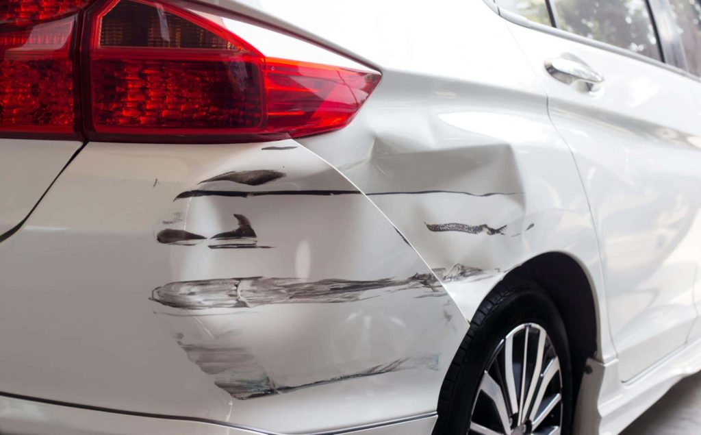 Close up of a car with a dented and scratched rear bumper. This type of damage will lead to the value of the car decreasing.