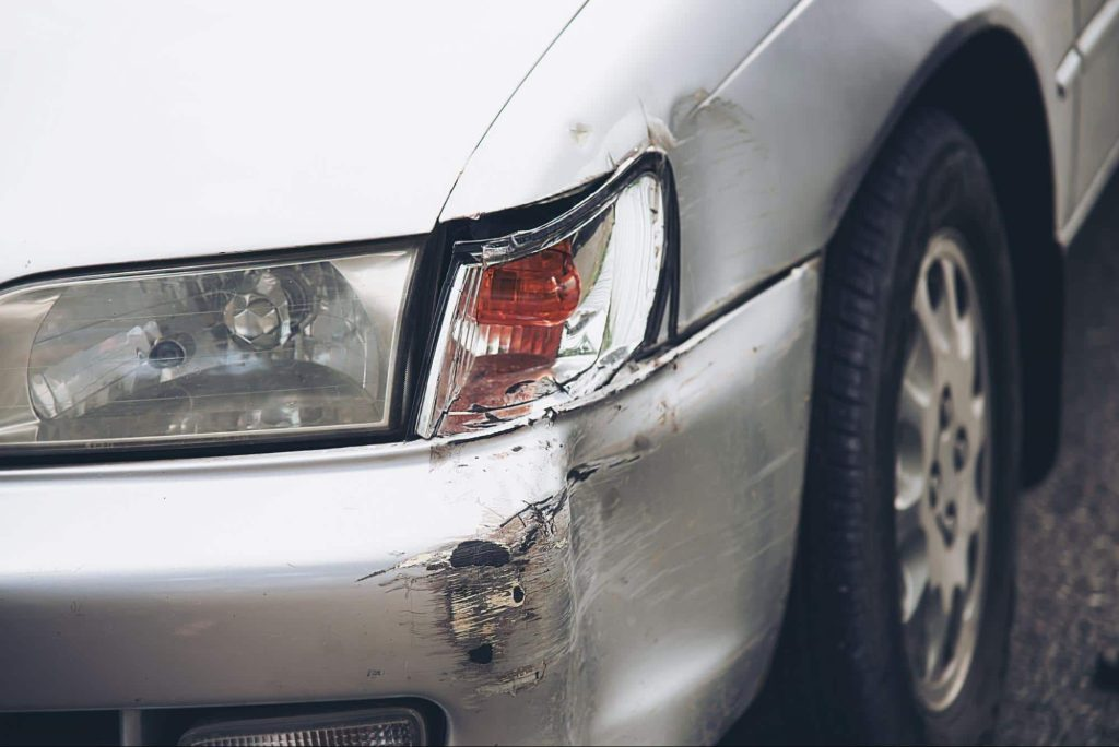 Close up of a car with a damaged front bumper and headlight after an accident that resulted in minor property damage.