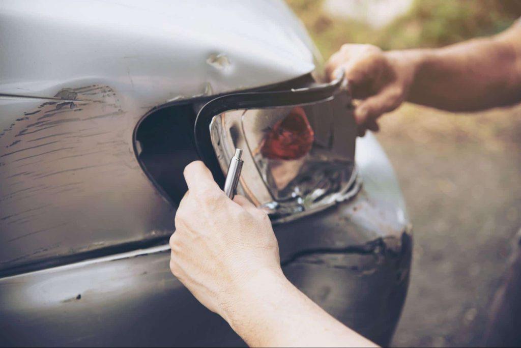 An insurance adjuster inspects a broken car headlight after a minor car accident.