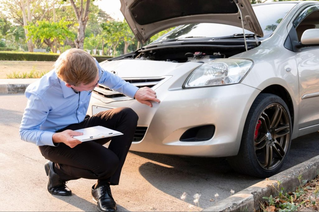 An insurance adjuster inspects a damaged car after a small accident.