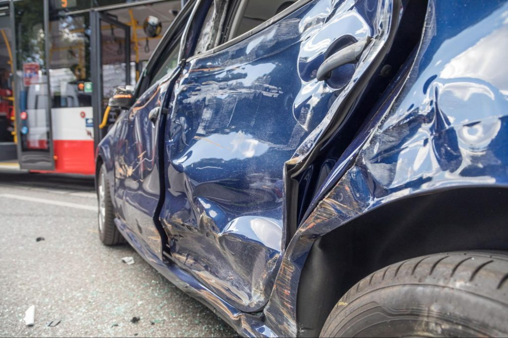 A blue car which has been totaled due to a side impact collision with an uninsured driver.