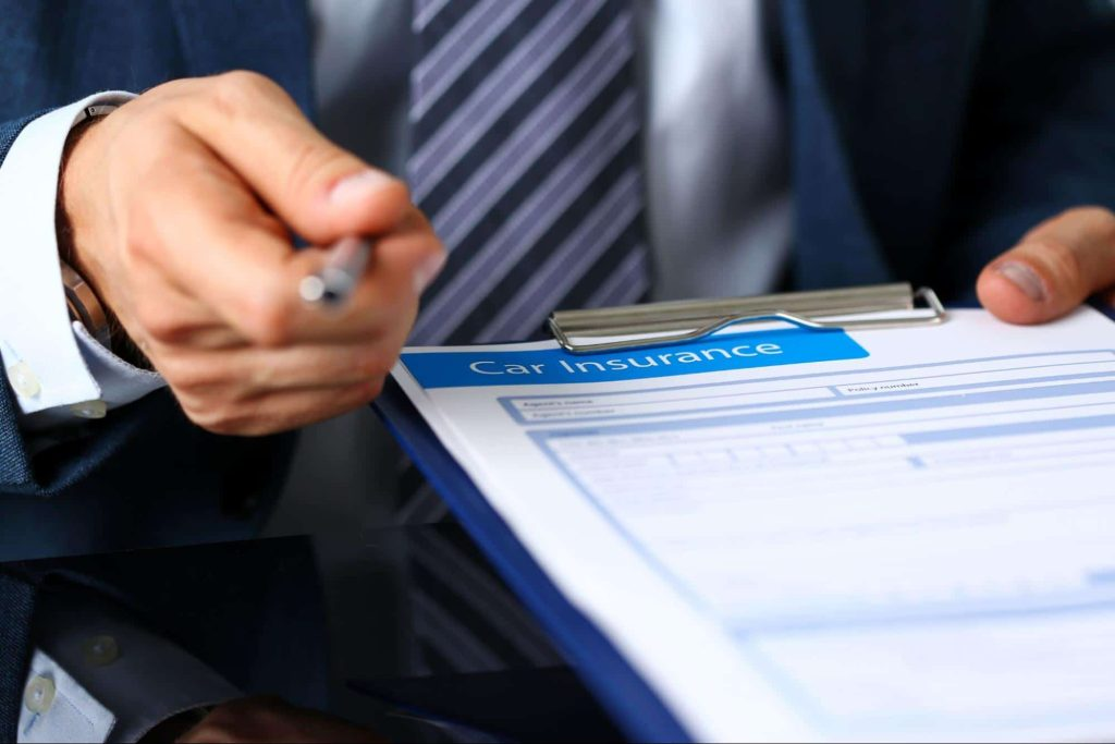 An insurance adjuster offers a pen and a car insurance form.