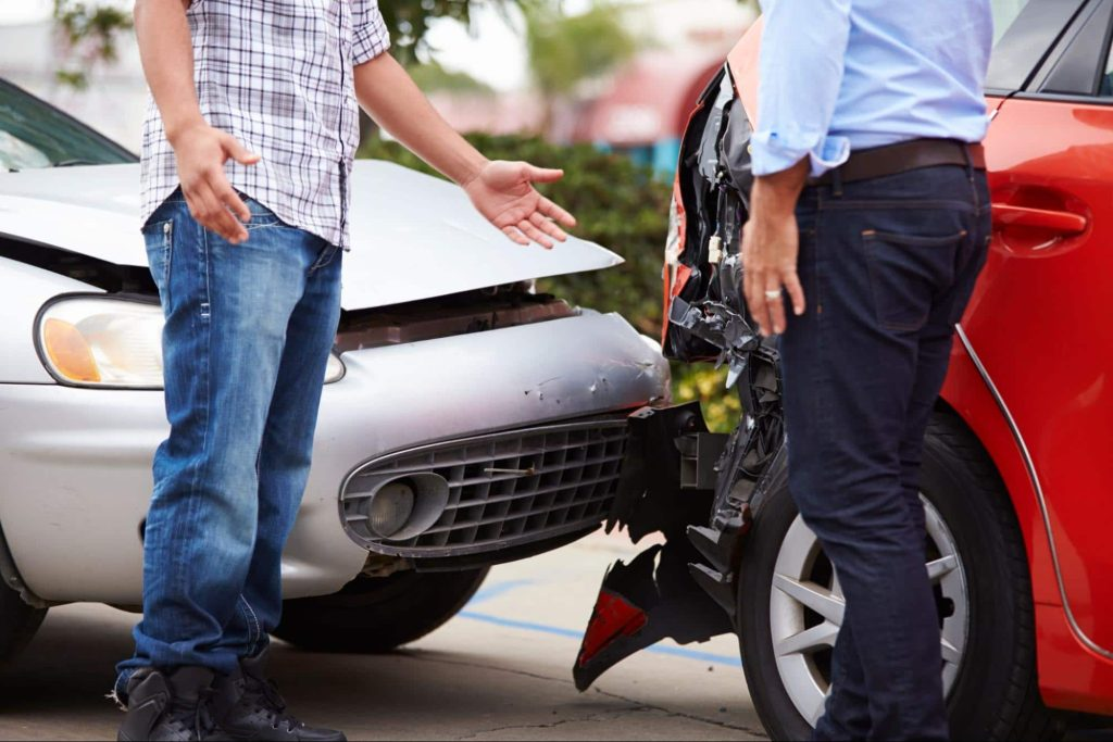 An insured driver and an uninsured driver exchange information at the scene of a rear end car accident.