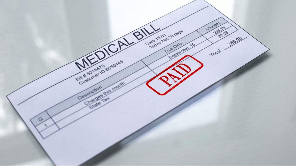 A paid medical bill sitting atop a glossy white table top.
