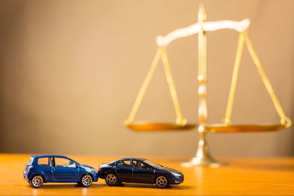 Toy cars on a wooden table arranged to look like a rear end car accident with the scales of justice in the background.
