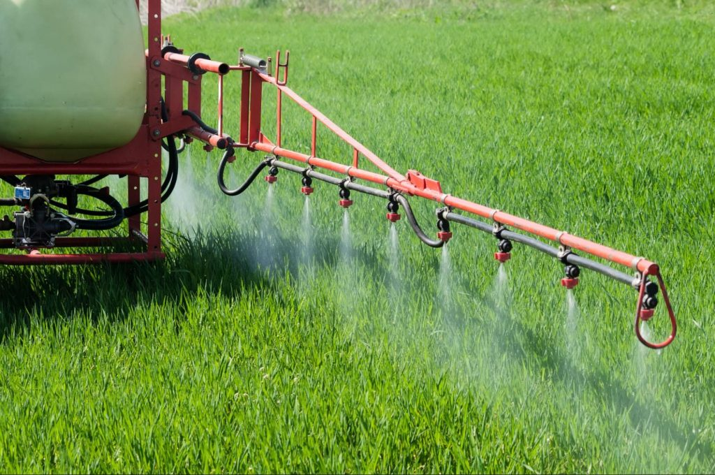 Tractor spraying Paraquat in a field.